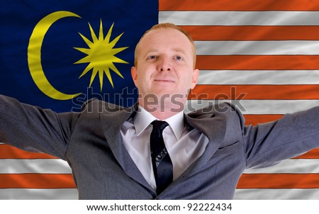 joyful investor spreading arms after good business investment in malaysia, in front of flag