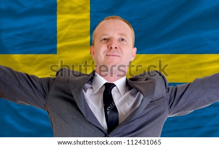 joyful investor spreading arms after good business investment in sweden, in front of flag