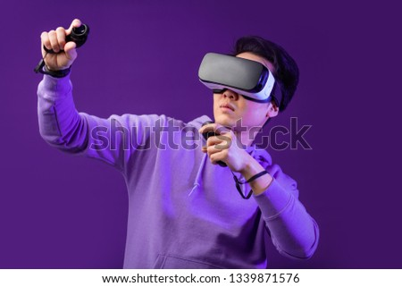 Joyful Japanese youngster playing videogame in virtual reality helmet on dark blue background. Smartphone using with virtual reality goggles. Technology, simulation, hi-tech, game concept