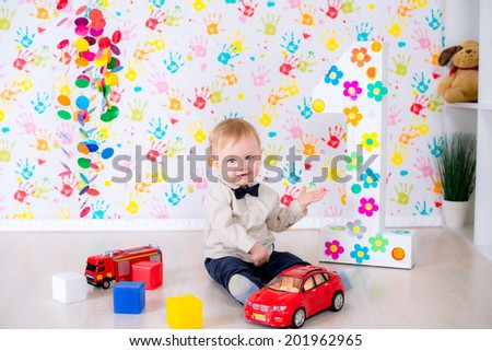 joyful kid boy on first birthday party with toy cars and blocks in the bright room have a fun game