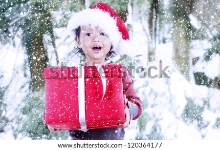 Joyful kid carrying Christmas present outdoor
