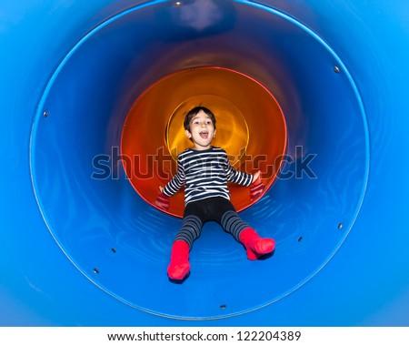 Joyful kid sliding in tube slide on playground