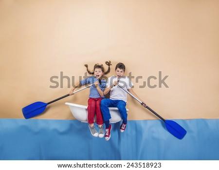 Joyful kids as sailors on the sea. Studio shot on a beige background.