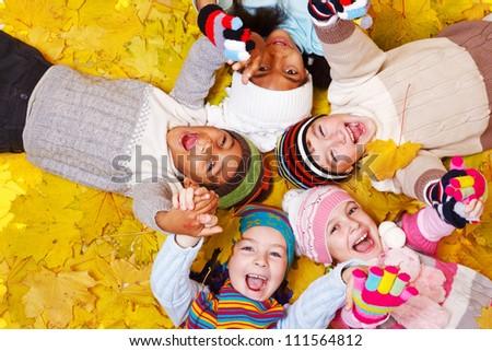 Joyful kids lie on yellow leaves
