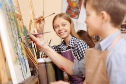 Joyful kids painting in the art school