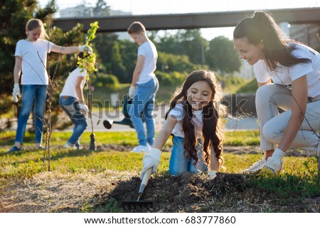 Joyful kids watering new tree #683777860