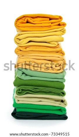 Joyful laundry. Pile of green and yellow folded clothes on white background.