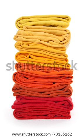 Joyful laundry. Pile of red and yellow folded clothes on white background.