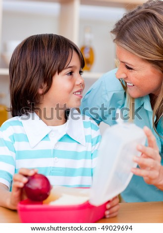 Joyful little boy and his mother preparing his snack in the kitchen
