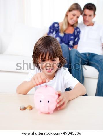 Joyful little boy inserting coin in a piggybank in the living room