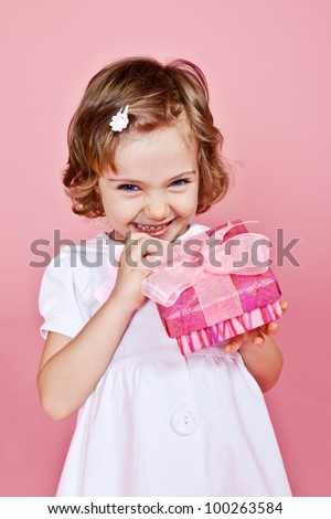Joyful little girl holding pink present in hands