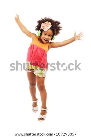 Joyful little girl in headphones is jumping