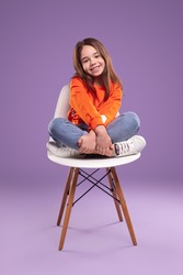 joyful little girl in orange sweater looking at camera with curiosity while sitting on chair with arms and legs crossed against violet background in studio