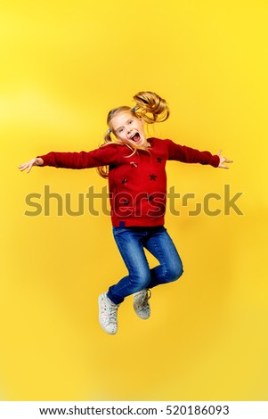 Joyful little girl jumping over yellow background. Happiness, activity and child concept. Copy space.
