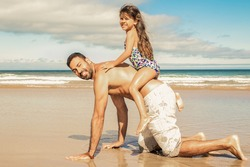Joyful little girl riding on dads back. Father going on hands and knees on beach. Side view. Family outdoor activities concept