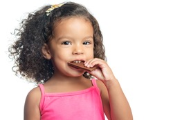 Joyful little girl with an afro hairstyle eating a chocolate bar isolated on white