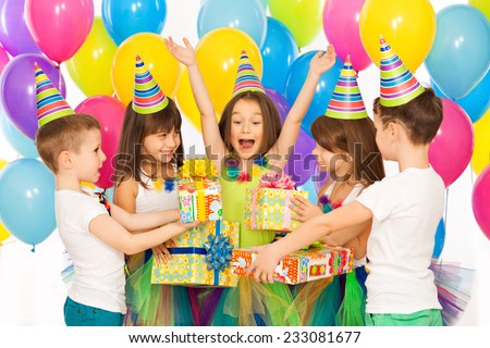 Joyful little kid girl receiving gifts at birthday party. Holidays, birthday concept.