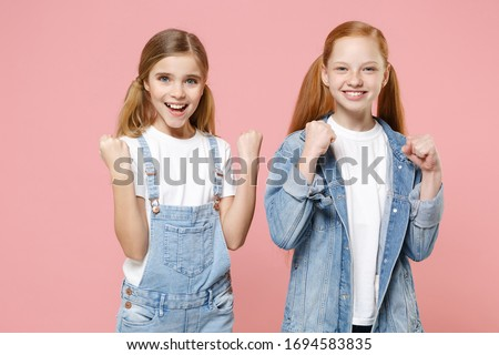 Joyful little kids girls 12-13 years old in white t-shirt, denim clothes isolated on pastel pink background children portrait. Childhood lifestyle concept. Mock up copy space. Doing winner gesture Stock photo ©
