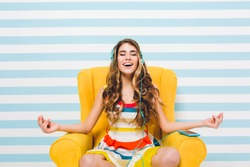 Joyful long-haired girl meditating while sitting in a lotus pose on blue striped background. Pretty young woman in colorful dress chilling in yellow armchair and listening relaxing music.