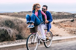 Joyful love friendship concept - happy adult caucasian, couple having fun with bicycle in outdoor leisure activity. concept of active playful people with bike during vacation - everyday joy lifestyle