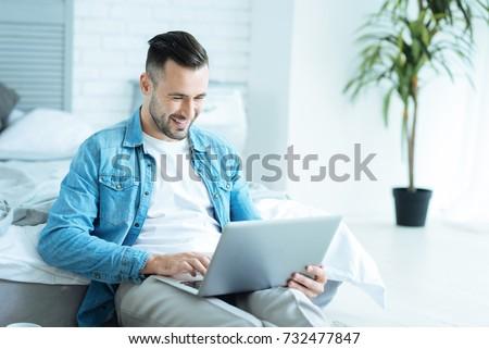 Joyful man grinning broadly while using laptop