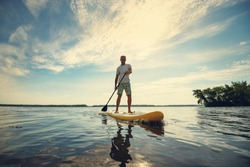 Joyful man is training  SUP board in large river on a sunny morning against a blue sky background . Stand up paddle boarding - awesome active outdoor recreation. Wide angle, backlight.