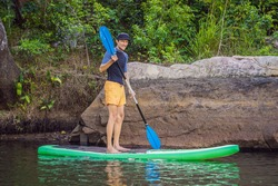 Joyful man is training SUP board in river on a sunny morning. Stand up paddle boarding - awesome active outdoor recreation