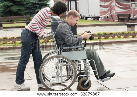 Joyful man on a wheelchair looking image in the camera