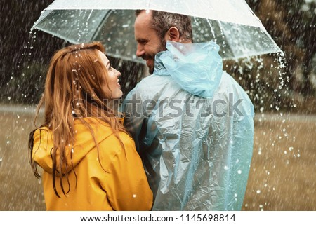 Joyful man strolling with woman in rain. They are looking at each other with content and love #1145698814