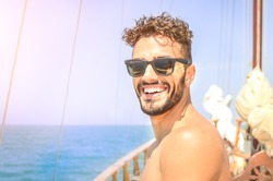 Joyful man take self portrait on exclusive luxury sailing boat. Concept of friendship and travel with young people. Happy guy spending time with friends during summer trip with bright sunny color tone