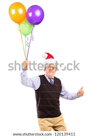 Joyful mature gentleman with christmas hat holding bunch of balloons and giving thumb up isolated on white background