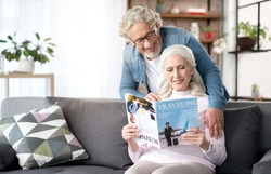 Joyful mature husband and wife entertaining at home together
