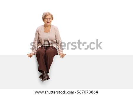 Joyful mature woman sitting on a panel isolated on white background