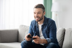 Joyful middle-aged bearded man playing video game with joystick at home, sitting on couch in living room, having fun at weekend, copy space. Home entertainment, leisure, domestic lifestyle