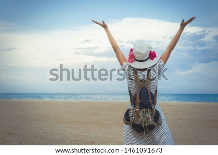 Joyful middle-aged woman in a dress raised her hands up on the ocean sea. Joy, pleasure, rest, freedom concept.