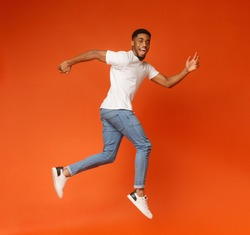 Joyful millennial african-american guy walking on air, jumping on orange studio background, smiling at camera
