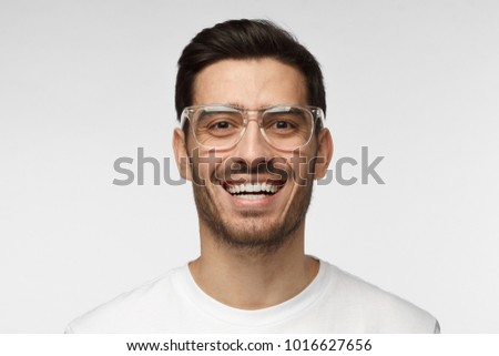 Joyful modern optimistic man smiles broadly, shows white perfect teeth. Positive emotions, facial expressions and happiness concept.  - Shutterstock ID 1016627656