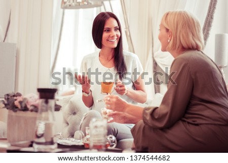 Joyful mood. Joyful young woman keeping smile on her face while enjoying pleasant conversation #1374544682
