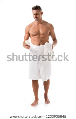 joyful muscular shirtless man wrapped in towel holding shower gel isolated on white