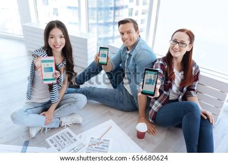 Joyful nice people doing showing you their smartphones