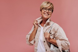 Joyful old lady with blonde short hairstyle and tanned skin in beige modern jacket smiling and holding cool bag on isolated backdrop..
