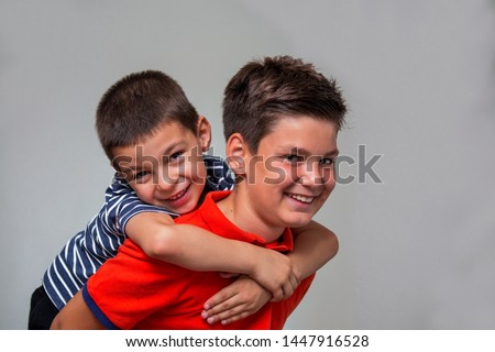Joyful older brother giving younger brother a piggy bag while playing and laughing with big expressions, having fun. Brother carrying younger brother kid on his back
