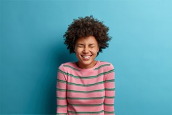 Joyful optimistic woman hears hilarious joke, closes eyes and smiles broadly, amused by silly anecdote, wears striped jumper, poses over blue background. Extremely happy millennial girl feels carefree