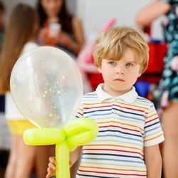 joyful or sad kid boy on birthday party with an air balloon, indoors. Animators on background.
