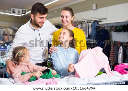 Joyful parents choosing new turtleneck for daughters in children clothing shop