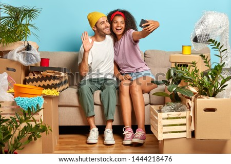 Joyful pleased girlfriend and boyfriend make selfie in their new apartment, waves in smartphone screen, have video call with friends, sit on couch with belognings. Young couple move into bought house