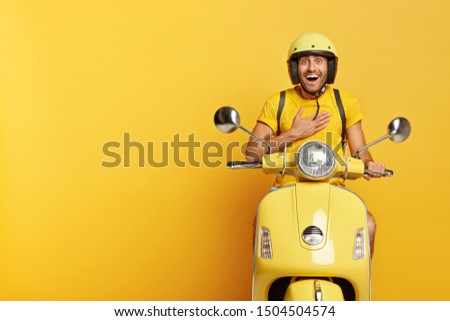 Joyful pleased man receives good news directly on his way, keeps hand on chest, wears helmet, poses on fast moped, isolated over yellow studio wall, blank space aside for your advertisement.
