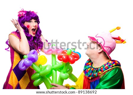 Joyful posing clowns in love with colorful flowers on isolated white