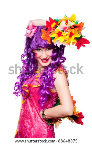 Joyful posing female clown with colorful flowers on isolated white