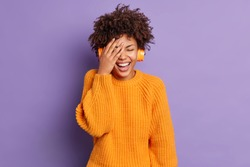 Joyful positive young African American woman makes face palm wears stereo wireless headphones listens audio track poses against vivid purple background. People happy emotions and leisure concept